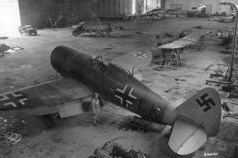 A US P-47 Thunderbolt in Luftwaffe markings and behind a P-51 Mustang being put back together at Gottingen-Weende